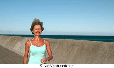 Senior woman jogging on a sunny day