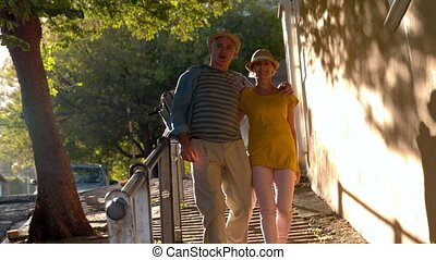 Senior couple walking down steps in the city in slow motion