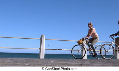Senior couple going on a bike ride in the city on the pier...