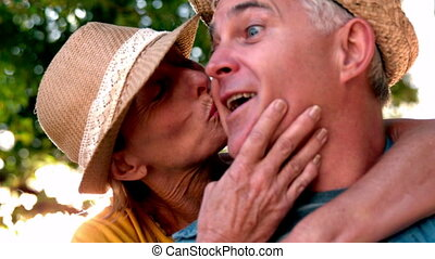 Senior woman giving her partner a kiss on sunny day in slow...