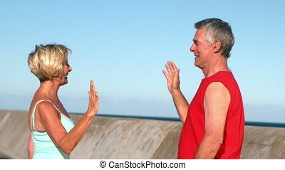 Senior couple high fiving after a jog in slow motion