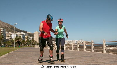 Senior couple roller blading along the pier in slow motion