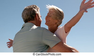 Senior couple hugging on sunny day in slow motion