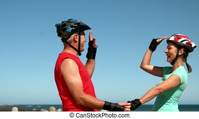 Senior couple roller blading along the pier and high fiving...