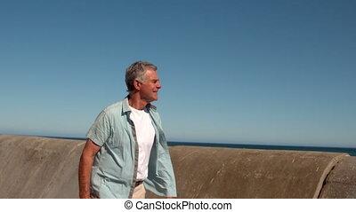 Senior man walking along the pier