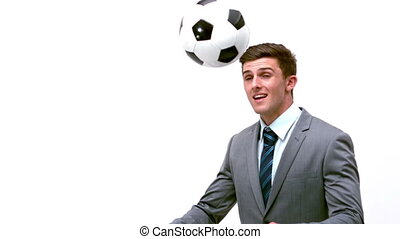 Young businessman heading football away in slow motion
