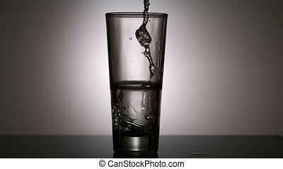 Water pouring into a glass in slow motion