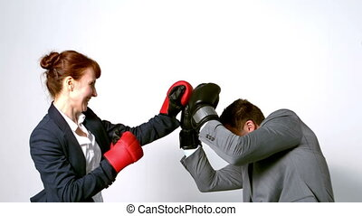 Young businesswoman punching colleague with boxing gloves in...