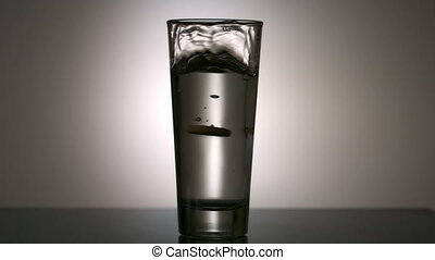 Effervescent vitamin tablet in glass of water in slow motion
