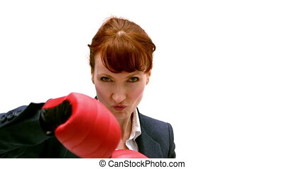 Young businesswoman punching with boxing gloves in slow...