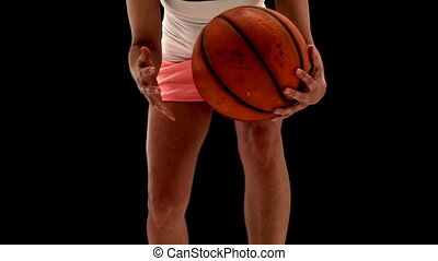 Fit young woman playing basketball
