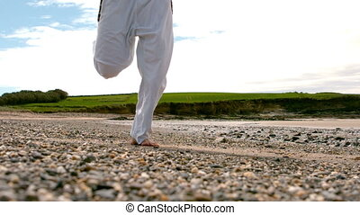 Man jogging barefoot by the coast in slow motion