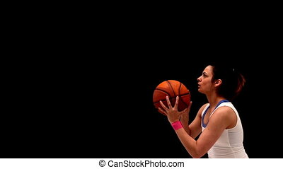 Fit young brunette playing basketball in slow motion