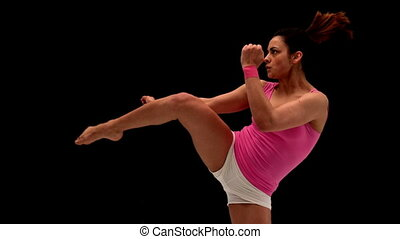 Fit young woman kicking