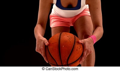 Fit young woman playing basketball in slow motion