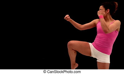 Fit young woman kicking on black background in slow motion