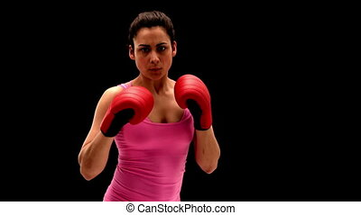 Fit young woman punching at camera on black background in...