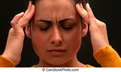 Sick young woman rubbing her head on black background in...