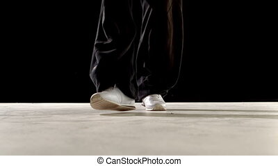 Cool young break dancer dancing on black background in slow...