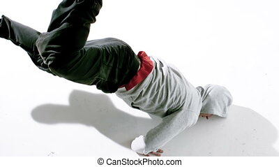 Cool young break dancer dancing on white background in slow...