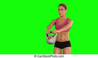Fit woman lifting up kettlebell in slow motion