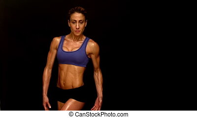Muscular woman flexing towards camera in slow motion