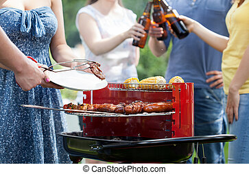 Friends having party with barbecue in a garden