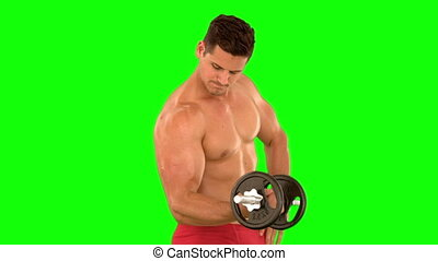 Muscular man lifting heavy dumbbell in slow motion