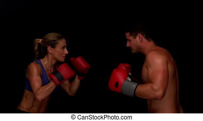 Strong couple punching towards each other in slow motion