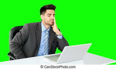Handsome businessman working at desk on green screen...