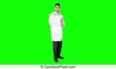 Young doctor standing with clipboard on green screen...
