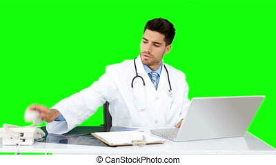 Young doctor working at his desk on green screen background