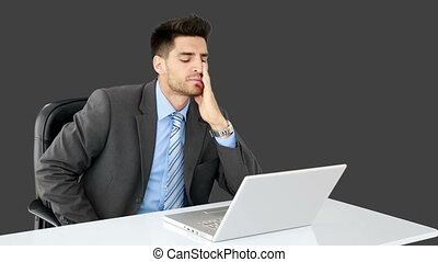Young businessman working at his desk on grey screen...