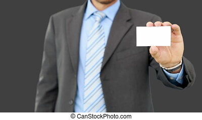 Young businessman showing card to camera on grey screen...