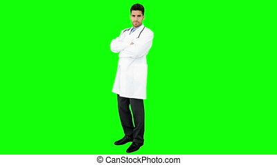 Young doctor looking at camera on green screen background
