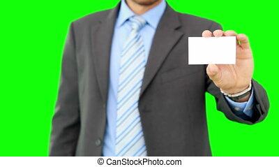 Businessman showing his business card on green screen...
