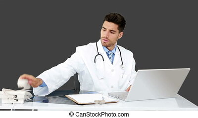 Young doctor working at his desk on grey screen background