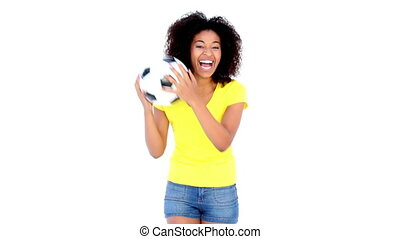 Pretty girl in yellow tshirt holding football on white...