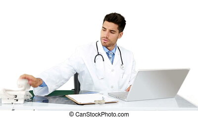 Young doctor working at his desk on white background