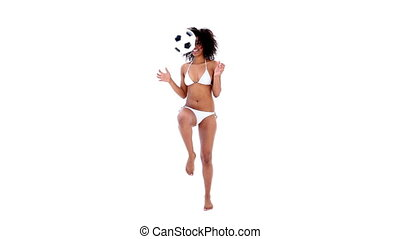 Pretty girl in bikini holding football on white background