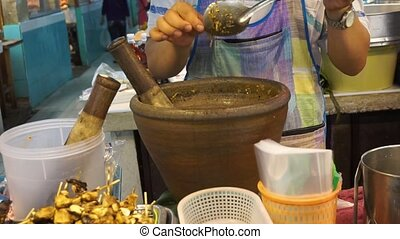 Making Thai chilli fresh paste in a mortar with pestle