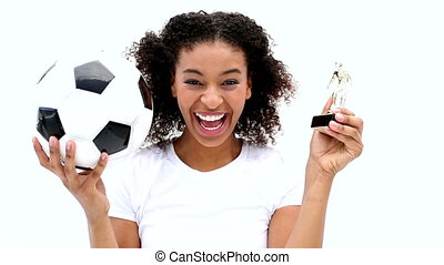 Pretty girl holding football and trophy on white background