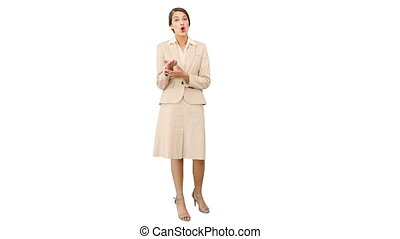 Young businesswoman talking at camera on white background
