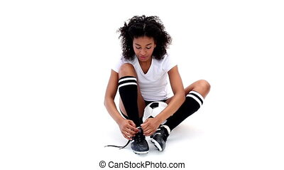 Pretty girl tying her football boots on white background