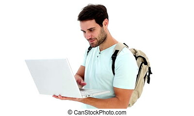 Handsome young student using his laptop on white background