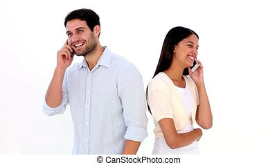 Attractive young couple talking on phones on white...