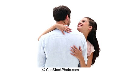 Attractive young couple hugging and smiling at camera on...