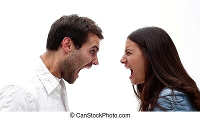 Angry young couple shouting at each other on white...