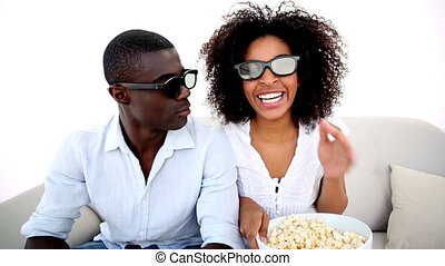 Couple watching a 3d movie at home in the living room