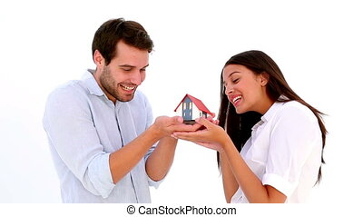 Attractive young couple holding mini house on white...